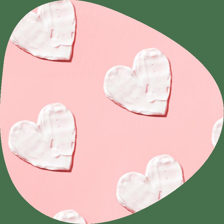 Herz Muster aus Creme auf rosa Hintergrund. Hautpflege