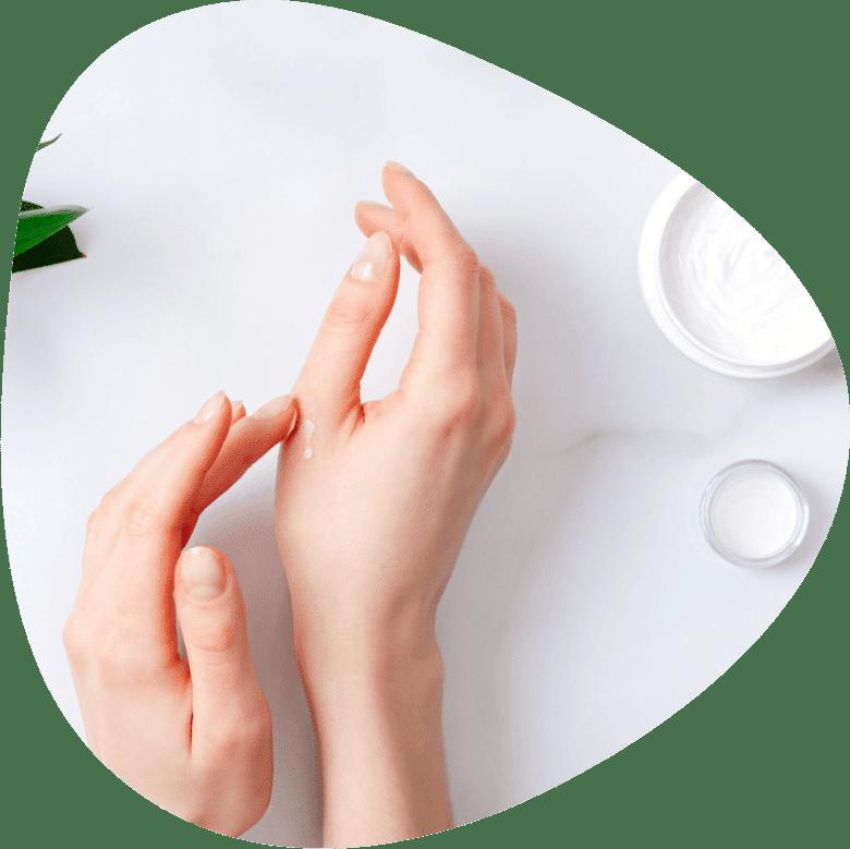 Frau cremt sich Hand ein